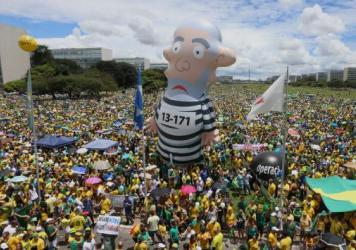 An inflatable figure in the likeness of Luiz Inacio Lula da Silva, former president of Brazil, is seen as demonstrators gather during a protest against current President Dilma Rousseff and the ruling Workers Party in Brasilia, Brazil, on Sunday. Hundreds of thousands of Brazilians gathered across the country on Sunday to protest political corruption and call for the impeachment of Rousseff.