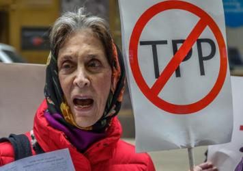 """A protester holds a """"STOP THE TPP"""" sign outside the New Zealand embassy in New York, where activists protested the TPP deal."""