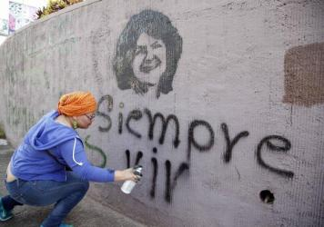 "A woman spray paints the phrase ""Always Alive"" below a stenciled image of slain environmental and indigenous rights activist Berta Cáceres in Tegucigalpa."
