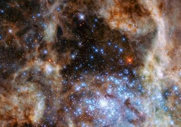 "A 2009 image from the Hubble shows the same star cluster. Here's how the space agency described it then: ""The brilliant stars are carving deep cavities in the surrounding material by unleashing a torrent of ultraviolet light, and hurricane-force stellar"
