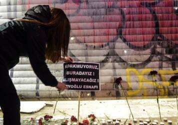 "A woman puts a placard at the site of a blast on Istiklal Street, a major shopping and tourist district, in central Istanbul, on Saturday. The sign reads in Turkish, ""We are not afraid, we are here, we won't adjust,"" according to an AFP translation."