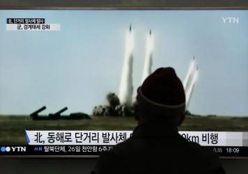 At South Korea's Seoul Railway Station, a man watches a TV screen showing footage of a missile launch conducted by North Korea.