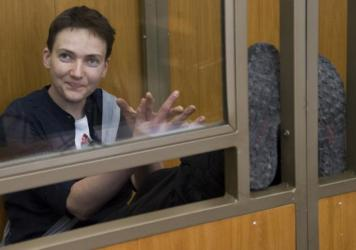 Ukrainian pilot Nadezhda Savchenko applauds and smiles in a glass cage inside court ahead of the verdict in the town of Donetsk, Rostov-on-Don region, Russia, on Tuesday.
