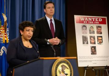 Attorney General Loretta Lynch and FBI Director James Comey stand by a poster showing Iranians who are wanted by the FBI for computer hacking during a news conference at the Justice Department in Washington on Thursday.