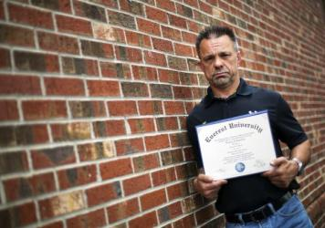"""Shane Satterfield, a roofer who owes more than $30,000 in debt for an associate's degree in computer science from one of the country's largest for-profit college companies that failed in 2014, holds his diploma in Atlanta. """"I graduated in April at the to"""