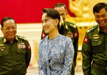 Myanmar's newly sworn in Foreign Minister Aung San Suu Kyi laughs along with top military officers, as her country marks a new step toward democracy Wednesday.