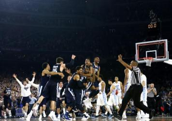 Villanova's Kris Jenkins is mobbed by teammates after hitting the game-winning three-pointer to defeat the North Carolina Tar Heels 77-74 in the NCAA title game Monday night.