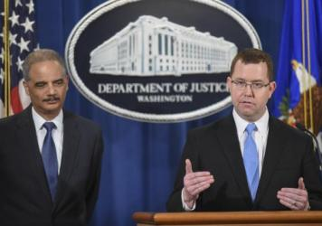 Then-acting Assistant Attorney General Stuart Delery (right) speaks at a news conference with Attorney General Eric Holder at the Department of Justice in 2015.