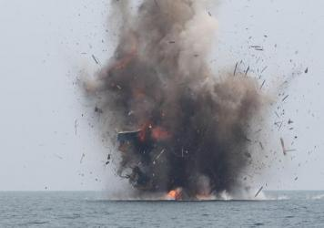 A foreign fishing boat that was caught in Indonesian territorial waters is blown up by Indonesian authorities in Kuala Langsa, Aceh Province on Tuesday. Indonesia sank more than 20 fishing boats Tuesday as part of a stepped up campaign against illegal fi