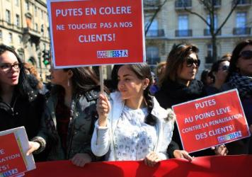 "Protesters hold signs reading, ""Prostitutes are angry. Don't touch our clients,"" during a protest Wednesday in Paris against legislation combating prostitution and sex trafficking."