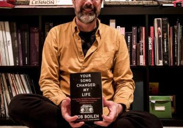 Bob Boilen holding a copy of his first book, <em>Your Song Changed My Life.</em>