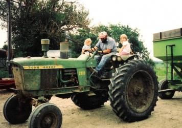 Karen (left) and Katie — still young girls at the time this photo was taken — sit with their father, Vern, on the family's tractor.
