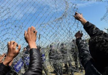 Refugees and migrants bearing Greek and German flags face Macedonian soldiers at the border fence as they protest on Monday, a day after violence broke out at the border.