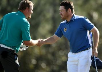 Louis Oosthuizen (right) shakes hands with his playing partner, J.B. Holmes, after the final round of the Masters on Sunday. Oosthuizen made an unlikely hole-in-one after his ball smacked Holmes' and then trickled into the cup.