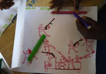 Young Nigerians draw an attack scene during a therapy program at a refugee camp in Chad for people displaced by the violent conflict with Boko Haram.
