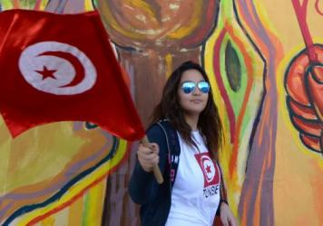 A Tunisian woman waves her national flag as international activists gather for the World Social Forum in Tunis on March 25, 2015.