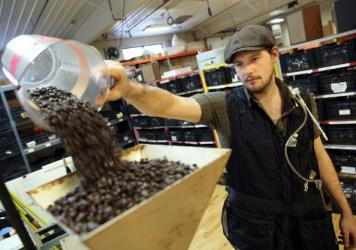 Just Coffee Cooperative's Benjamin Lisser prepares to grind coffee. The glass tube on his vest tests the air in his breathing zone for diacetyl, a chemical byproduct of the coffee roasting process that can cause lung disease.