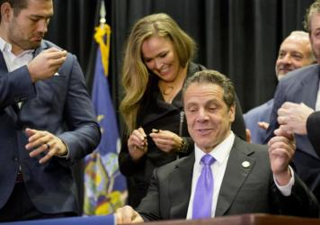Gov. Andrew Cuomo (center) signed into law a measure that will allow professional mixed martial arts in New York. Behind him are UFC athletes Chris Weidman (left) and Ronda Rousey.