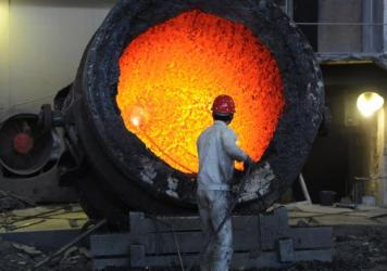 A worker stokes a burning cauldron at a steel mill in Hefei, in eastern China's Anhui province in 2011. Chinese steelmakers are overproducing, hurting prices and jobs, U.S. Commerce Secretary Penny Pritzker says.