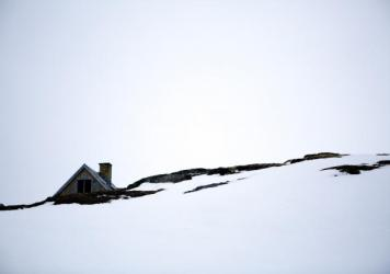 An abandoned house appears over a snow-covered hill in the old town of Kangeq, Greenland.