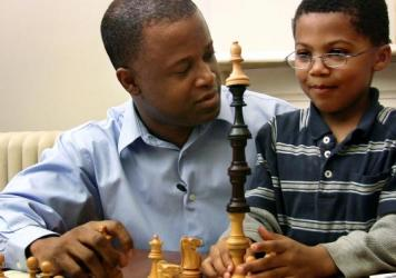 Maurice Ashley (right) shakes the hand of a student after defeating him in a friendly match at Walnut Grove Elementary School in Ferguson, Mo.