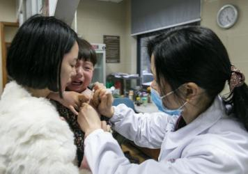 A woman holds her child to receive rabies vaccines at Hangzhou Hospital for the Prevention and Treatment of Occupational Disease as the child got scratched by a cat on March 22, 2016 in Hangzhou, Zhejiang Province of China. A case of illegal vaccines tha