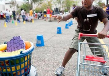 "A child runs a shopping cart relay during an Education Department summer enrichment event, ""Let's Read, Let's Move."" The 2012 event was part of a summer initiative to engage youths in summer reading and physical activity, and provide them information abo"