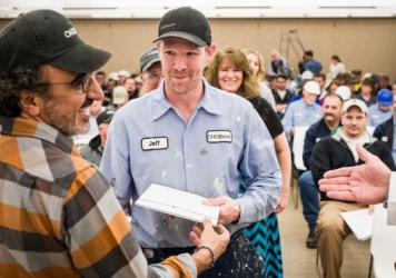 Chobani CEO Hamdi Ulukaya (left) presents an employee with shares of the company on Tuesday at the Chobani plant in New Berlin, in upstate New York.