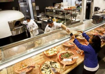A customer receives a slice of pizza from the prepared food section of the new Whole Foods Market Inc. store in downtown Los Angeles. Prepared foods sold at supermarkets, big-box and convenience stores are a bigger and bigger portion of those companies'