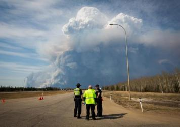 Officers look on as smoke from Fort McMurray's wildfires billows into the air in Alberta, Canada on Wednesday.