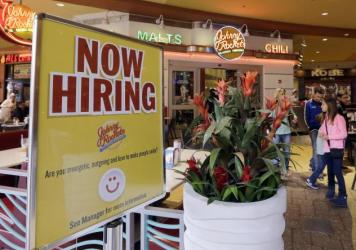 A restaurant posts a sign indicating it is hiring in Miami.