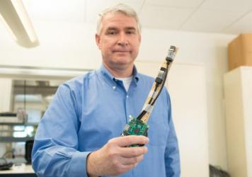 Dartmouth College researcher Timothy Pierson holds a prototype of Wanda, which is designed to establish secure wireless connections between devices that generate data.
