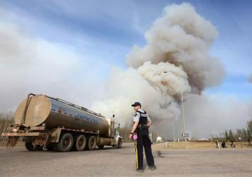 A police officer works a road block on Highway 63 near Fort McMurray, Alberta, on Friday.