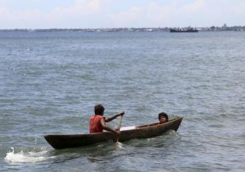 Two young men ride in a dug out canoe just off shore in Honiara, Solomon Islands, in 2012.