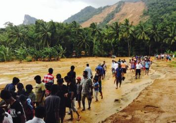 Sri Lankans slogged through the mud after massive landslides crashed down onto three villages in central Sri Lanka.