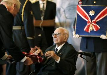 John Fieldsend, 84, with a photo he keeps on his fireplace mantel of Nicholas Winton, the man who saved his life. Fieldsend, born Hans Heini Feige, was one of 669 mostly Jewish children whom Winton rescued from Czechoslovakia just prior to World War II.