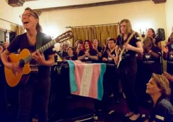 Transgender choruses — such as the Trans Chorus of Los Angeles, led by Lindsey Deaton (with guitar) — are springing up all over the country. A transgender pride flag is at the center of this image.