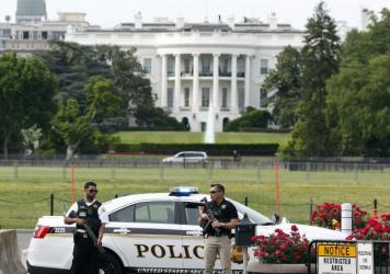 Law enforcement personnel stand south of the White House on Constitution Ave., in Washington, D.C., on Friday,. The White House was placed on a security alert after a Secret Service officer shot a man brandishing a firearm near a security checkpoint on a