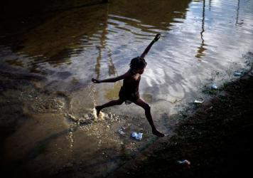 A little girl jumps across a flooded field containing the sewage runoff from the Mais Gate Camp after heavy rains in Port-au-Prince in 2010.