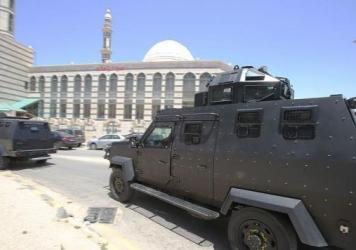 Jordanian anti-terrorism units pass in front of the intelligence services office at the Baqaa refugee camp north of Amman following Monday's terrorist attack.