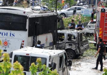 Police officers and rescuers inspect the site of a bomb attack that targeted a police bus in the Vezneciler district of Istanbul on Tuesday.