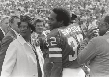 O.J. Simpson with his mother, Eunice, and father, Jimmy Lee, on the field at Rich Stadium for his induction into the Buffalo Bills Wall of Fame in 1980.