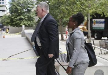 "Rear Admiral Robert J. Gilbeau, left, enters a federal courthouse in San Diego where he pleaded guilty to lying to federal investigators in the ""Fat Leonard"" navy bribery trial."