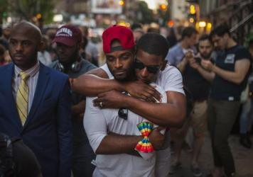 A couple hugs as people gather in front of a makeshift memorial in New York to remember the victims of the mass shooting in Orlando, Fla. on Sunday.