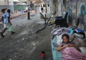 "Vanessa, currently homeless, rests on a Rio de Janeiro street on Friday where construction of a new light rail system has been delayed. The state government of Rio de Janeiro today declared a state of ""calamity"" ahead of the Rio 2016 Olympic Games which begin August 5."