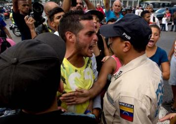An angry man outside a grocery store argues with a policeman in Caracus, Venezuela, on June 8 amid the country's ongoing food shortages. After waiting for hours, customers began protesting, an increasingly common occurence in Venezuela, which is suffering a severe economic crisis.