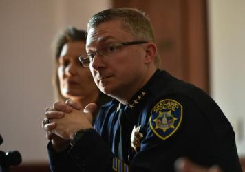 Oakland Police Chief Sean Whent, with Mayor Libby Schaaf behind him, listens to questions from the media  on May 2, 2015, after May Day protests in Oakland, Calif. Whent has since resigned as police chief — as did two interim chiefs after him, over the course of a little more than a week.