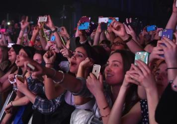 "Concertgoers use their cellphones during a Fifth Harmony concert March 23, 2015, in New York. The company Yondr created a locking pouch to hold phones during performances, creating a ""phone-free zone."""