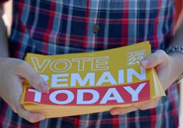 "A young man hands out ""Remain"" leaflets outside the polling station at Notre Dame Primary School on Thursday in Glasgow, Scotland. As a nation, Scotland voted to remain in the EU; but as a whole, the United Kingdom opted to leave."