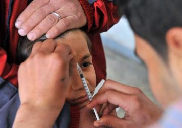 """A Syrian boy in a clinic in Aleppo receives an injection for the """"Aleppo button"""" — one of the names used for the welts caused by leishmaniasis."""